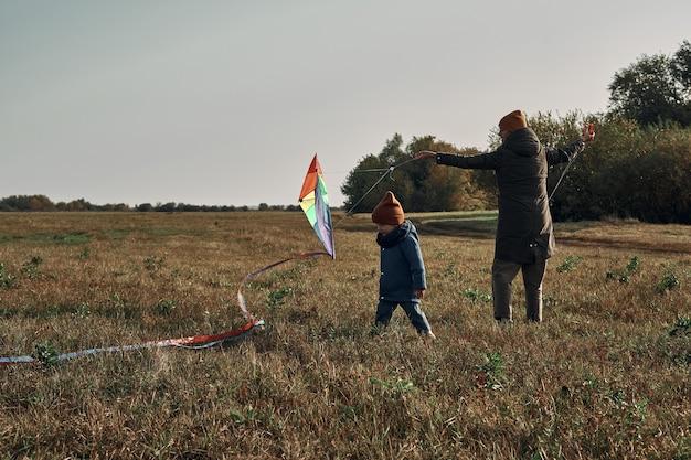 Een vrouw met een tweejarig kind vliegt vliegeren. games met kinderen, moederschap.