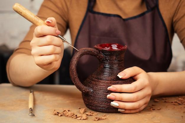Een vrouw met een vaas van klei in een pottenbakkerij. de pottenbakker versiert de pot met patronen. een concept van inspiratie en creativiteit. bruine vaas van klei in de handen van de pottenbakker close-up.