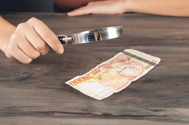 Een vrouw met een vergrootglas kijkt naar een bankbiljet