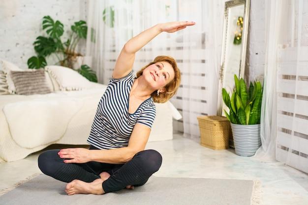Een vrouw met een volwassen uiterlijk doet thuis in sportkleding aan sport op de mat