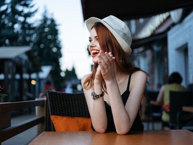 Een vrouw met een witte hoed en een zwarte jurk aan een tafel in een café op straat