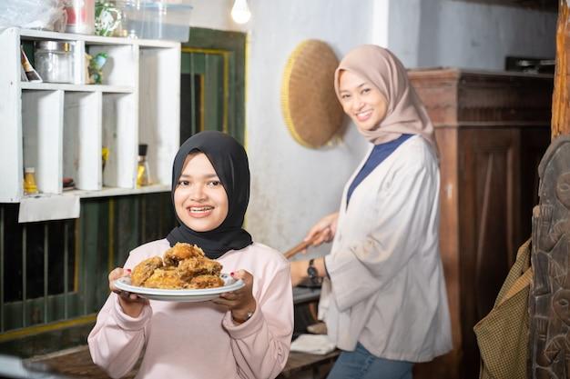 Een vrouw met een zwarte hoofddoek glimlacht terwijl ze een bord gebakken kip draagt