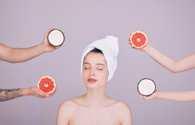 Een vrouw met gesloten ogen op de achtergrond, exotisch fruit om haar heen.