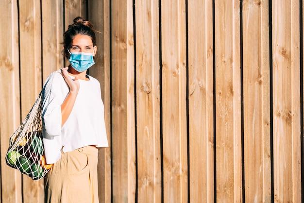 Een vrouw met groene ogen met een gezichtsmasker en een herbruikbare boodschappentas van mesh