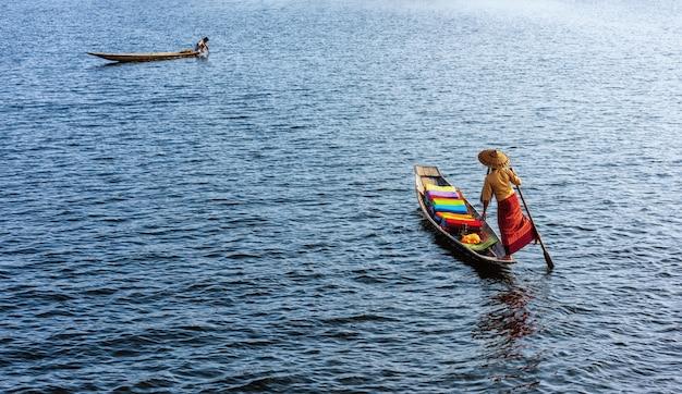 Een vrouw met handgemaakte kleurrijke lotusstoffen op haar boot in het dorp dain khone, aan het inlemeer, myanmar.