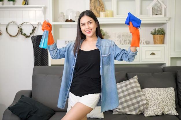 Een vrouw met het schoonmaken van handschoenen die alcoholspray ontsmettingsmiddel gebruiken om huis, gezond en medisch, covid-19 bescherming thuis concept schoon te maken.