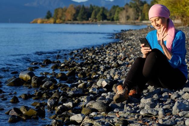 Een vrouw met kanker die een roze hoofddoek draagt, voert een videogesprek met haar mobiele telefoon op het strand