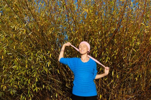 Een vrouw met kanker die in een bos met gele herfstbladeren glimlacht, bindt haar roze sjaal vast