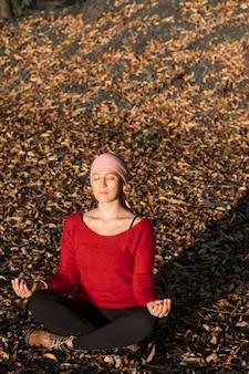 Een vrouw met kanker die tijdens een zonsondergang op een weide met droge bladeren mediteert.