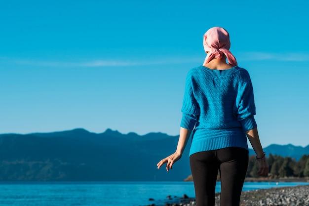 Een vrouw met kanker op haar rug met een roze hoofddoek en een blauwe jas kijkt naar het meer