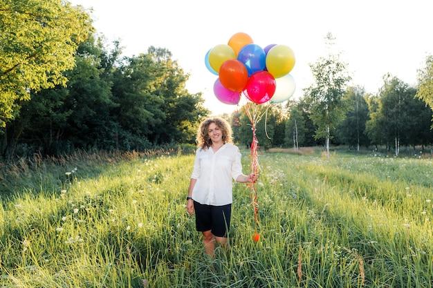 Een vrouw met krullend haar houdt regenboogballonnen in haar handen. mooi meisje op het gras in het park.