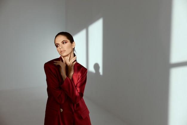 Een vrouw met lichte make-up en een rood jasje in een donkere kamer
