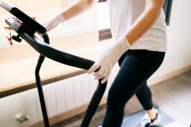 Een vrouw met masker en handschoenen slanke atleet oefent thuis lopend op de loopband