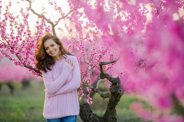 Een vrouw met natuurlijke schoonheid close-up kijkt naar de camera tegen de achtergrond van een lente jonge bloeiende tuin