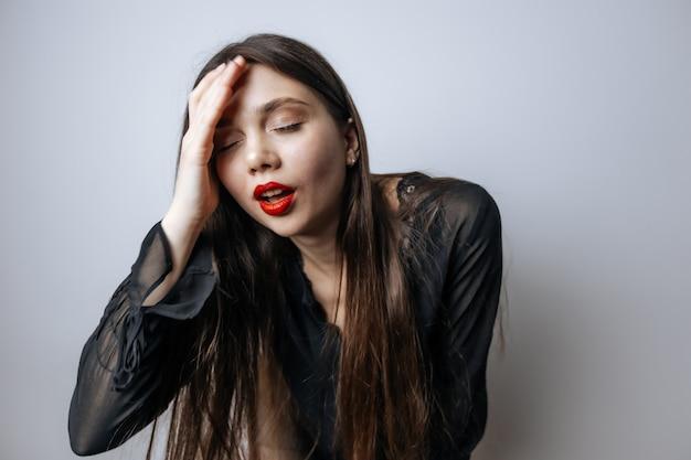 Een vrouw met rode lippen houdt haar hoofd vast