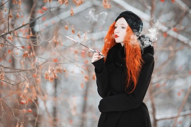 Een vrouw met rood haar in een zwarte jas op de achtergrond van een winter forest met een mondstuk in de hand. roodharige meisje met heldere uitstraling met een tulband op haar hoofd met een sigaret. esthetiek van roken