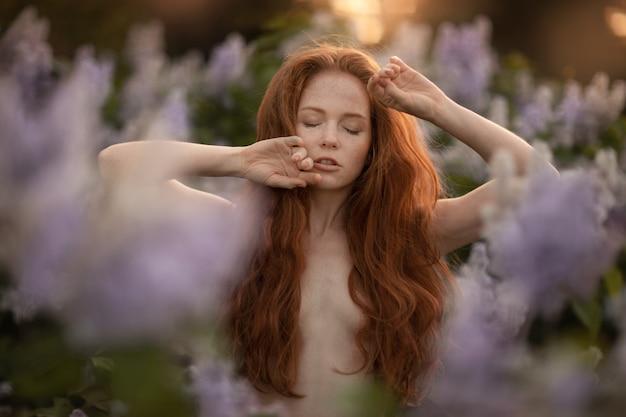Een vrouw met rood haar lang en krullend in een struik met paarse bloemen