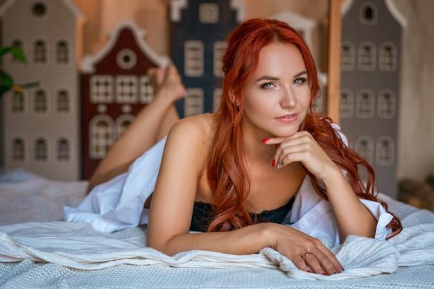 Een vrouw met rood haar ligt op een bed in zwart ondergoed en een wit overhemd