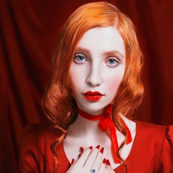 Een vrouw met rood krullend haar in een rode jurk en retro make-up op een rood. roodharig meisje met bleke huid, blauwe ogen, een heldere ongewone verschijning, rode lippen en rood lint rond de nek.