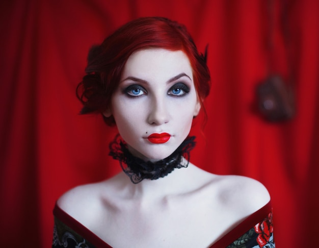 Een vrouw met rood krullend haar in een zwarte jurk en retro make-up op een rood.