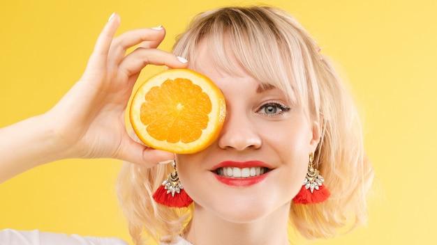 Een vrouw met sinaasappels in haar ogen. rode lippenstiftlippen. vrolijk, vrolijk meisje straalt positieve, verwende sinaasappels uit. geïsoleerd op gele achtergrond