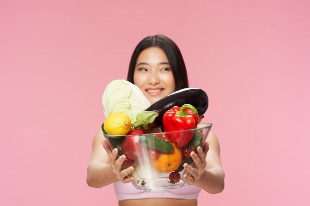 Een vrouw met vers voedsel in een plaat glimlacht