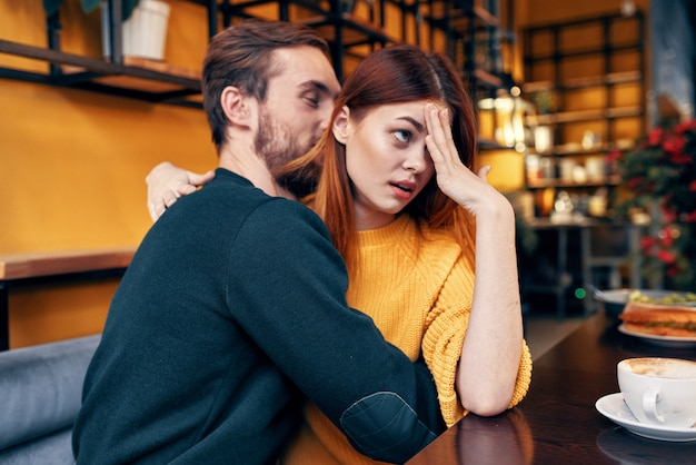 Een vrouw met walging omhelst een man in een trui aan een tafel in een café