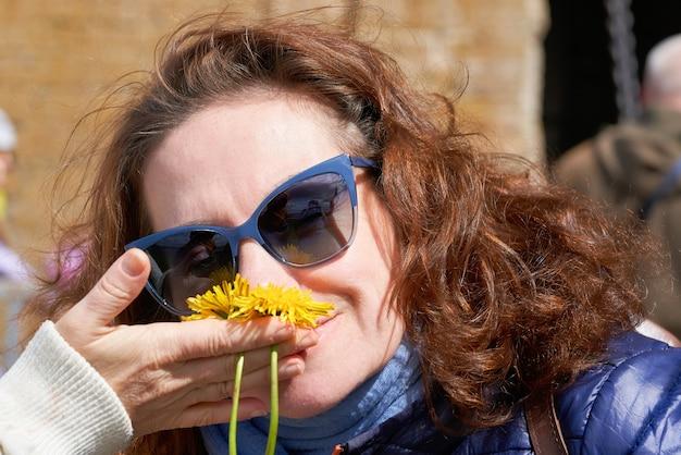 Een vrouw met zonnebril snuift gele paardenbloembloemen