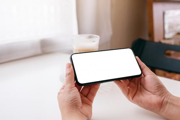 Een vrouw met zwarte mobiele telefoon met lege desktop scherm met koffie glas op tafel