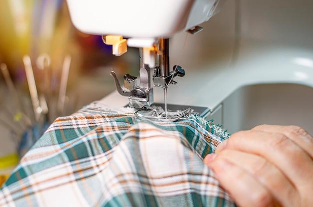 Een vrouw naait op een naaimachine. werk plaats. detailopname.