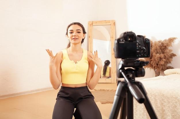 Een vrouw neemt een video op voor haar kanaal op internet. blogger. emotioneel meisje praat