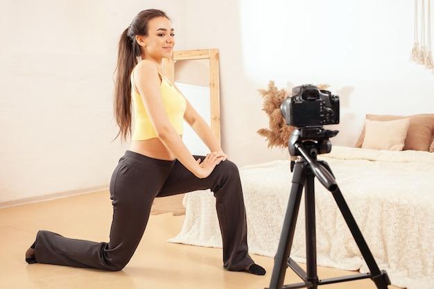 Een vrouw neemt een video op voor haar kanaal op internet. blogger. laat zien hoe u op de juiste manier oefent