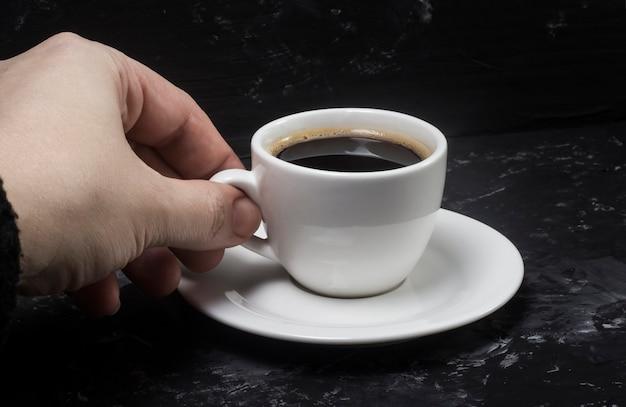 Een vrouw neemt een witte kop met zwarte aromatische koffie in haar handen om van de smaak te genieten.