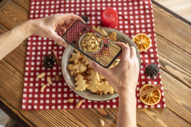 Een vrouw neemt foto's op een bord met heerlijke zelfgemaakte kerstkoekjes op haar telefooncamera