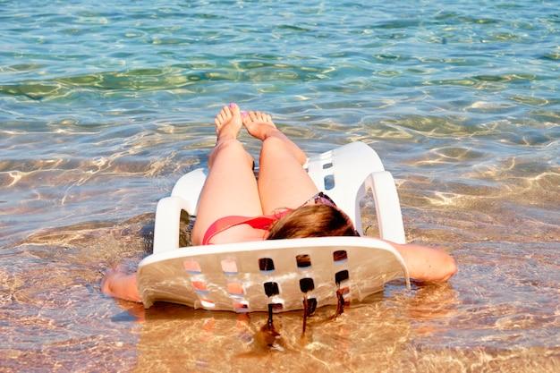 Een vrouw ontspant zich, comfortabel liggend op een chaise longue in het water van de zee
