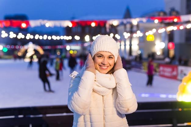 Een vrouw op de ijsbaan schaatst en neemt selfie op smartphone. oudejaarsavond en kerst. fairy lichten. ijs en sneeuw stemming concept. winter