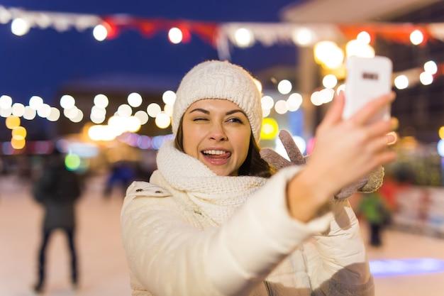 Een vrouw op de ijsbaan schaatst en neemt selfie op smartphone. oudejaarsavond en kerst. fairy lichten. ijs en sneeuw stemming concept. wintersport.