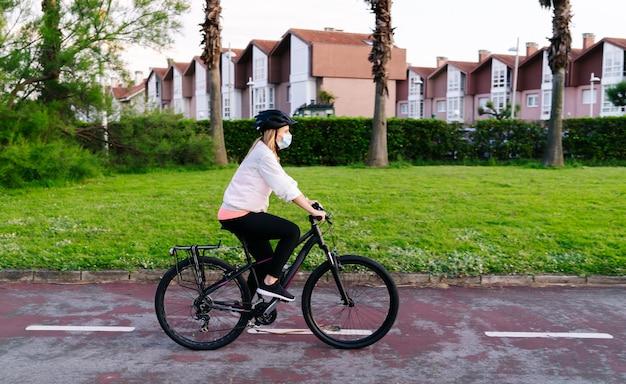 Een vrouw op een fiets met veiligheidsmasker op haar gezicht