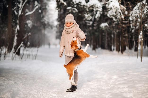 Een vrouw op een winterse dag met haar hond beagle in de winter bos spelen.