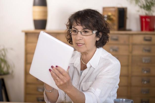 Een vrouw op middelbare leeftijd die een computertablet gebruikt