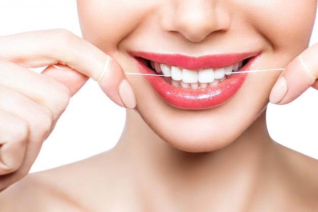 Een vrouw poetst haar tanden met tandzijde.