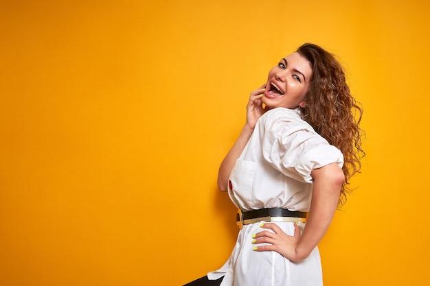 Een vrouw poseert. een jonge gelukkige vrouw met krullend haar geniet van het leven. emotioneel lacht, lacht. ze draagt een wit overhemd.