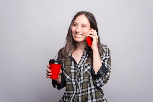Een vrouw praat met haar telefoon die glimlacht en een kopje met warme drank vasthoudt bij een grijze muur