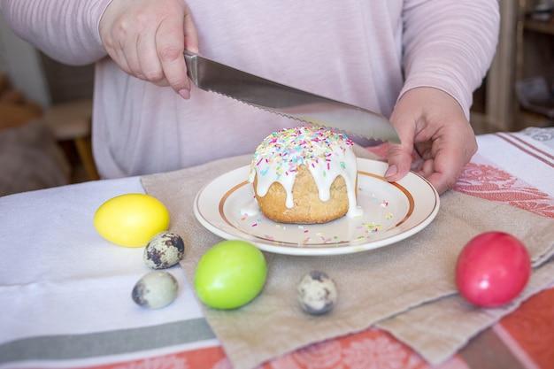 Een vrouw proeft een traditionele paascake en snijdt een taart met een mes. gekleurde eieren op een tafel