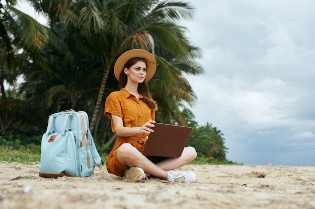 Een vrouw reist met een laptop langs de oceaan langs het zand met palmbomen