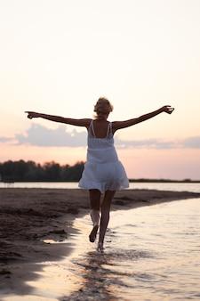 Een vrouw rent langs het strand foto achteraanzicht van een mooie gelukkige blonde in een witte zomerjurk op ...