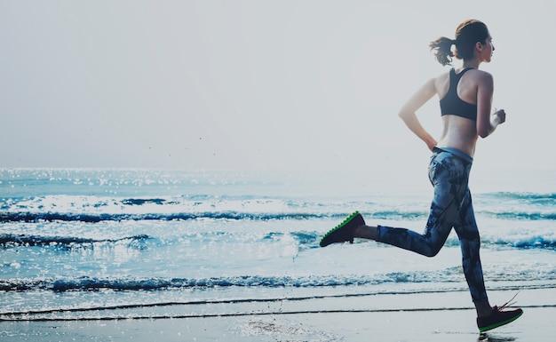 Een vrouw rent op het strand