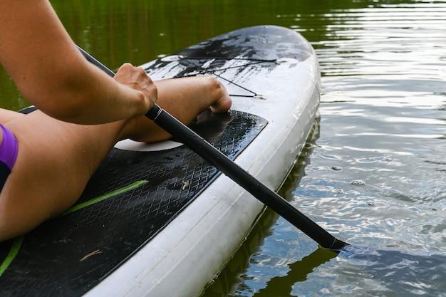 Een vrouw rijdt op de sup board door een smal kanaal omgeven door dicht gras. actieve weekendvakanties wilde natuur buiten. een vrouw zit met gestrekte benen.