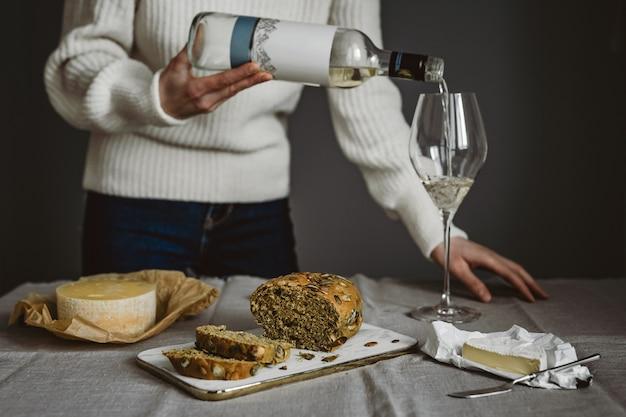 Een vrouw schenkt een glas witte wijn uit een fles, verschillende soorten kaas en brood op tafel. horizontale levensstijlfoto