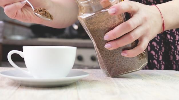 Een vrouw schenkt oploskoffie in een kopje. selectieve aandacht. natuur